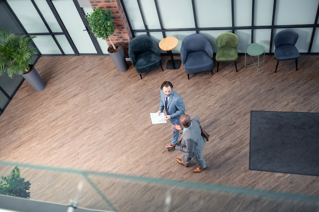 Entrando en el centro de negocios. vista superior de dos prósperos hombres de negocios que ingresan al centro de negocios antes de la reunión