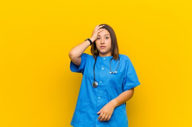 Entrando en pánico por una fecha límite olvidada, sintiéndose estresado, teniendo que cubrir un desastre o error aislado contra la pared amarilla