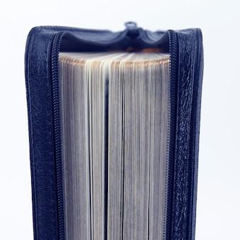 Entreabierta está la biblia sobre un fondo blanco. misterio cerrado libros sabios