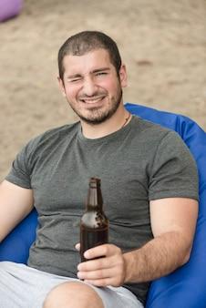 Entrecerrar los ojos al hombre con cerveza en la playa