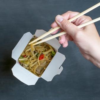 Entrega de almuerzos calientes en cajas. fideos de arroz con pollo y verduras sobre un fondo negro.