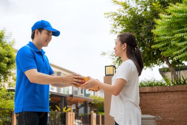 Entrega asiática joven en uniforme azul dando una caja al cliente