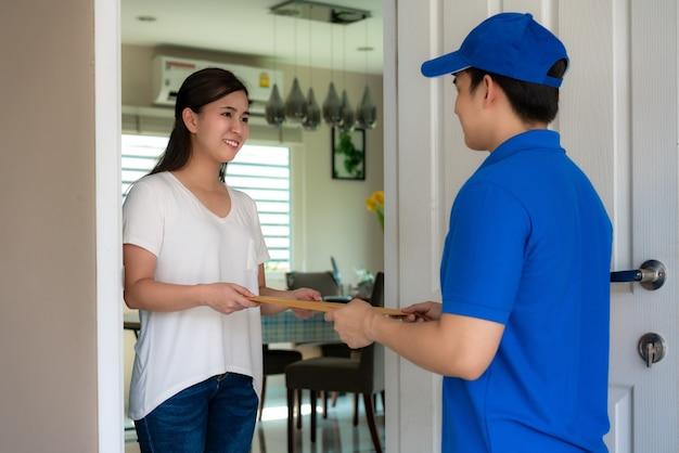 Entrega asiática joven en uniforme azul con documentos en frente de la casa