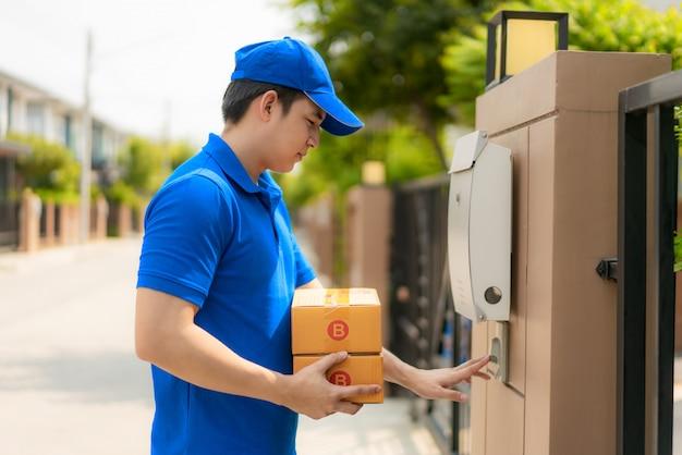 Entrega asiática joven en uniforme azul sosteniendo una caja