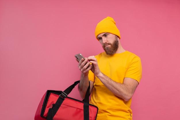 Entrega de comida indignado y disgustado mirando el teléfono en rosa