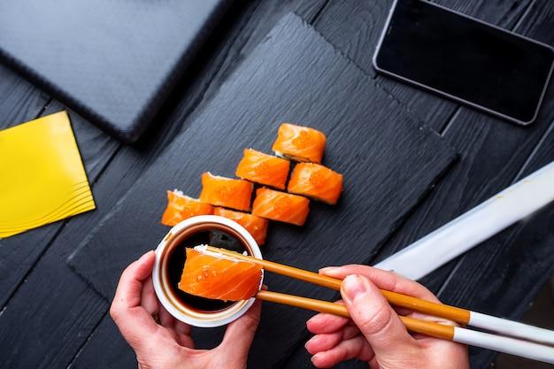 Entrega de comida a la oficina. set de sushi con salmón rodeado de accesorios de oficina: computadora portátil, teléfono. merienda saludable de oficina. mano con palillos remoja sushi en salsa de soja