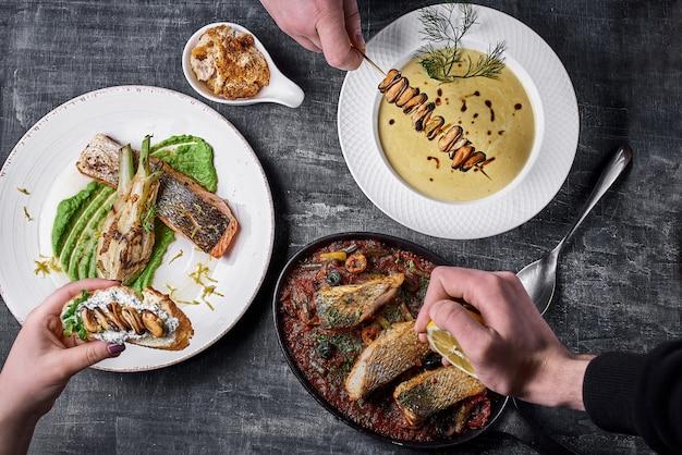 Entrega comida perca, pica de salmón, guiso de perca. menú dietético. menú de pescado mariscos. concepto de comida sana.