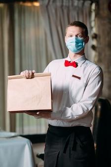 Entrega de comida desde el restaurante. retrato de un camarero con una bolsa de papel artesanal para la entrega de alimentos.
