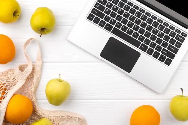 Entrega de compras en línea de comestibles. bolsa ecológica natural con frutas y laptop en mesa de madera