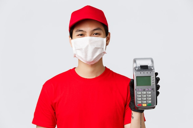 Entrega sin contacto, compra segura y compras durante el concepto de coronavirus. cerca del servicio de mensajería asiática en máscara médica y guantes protectores dan al cliente que paga la orden de compra de la terminal