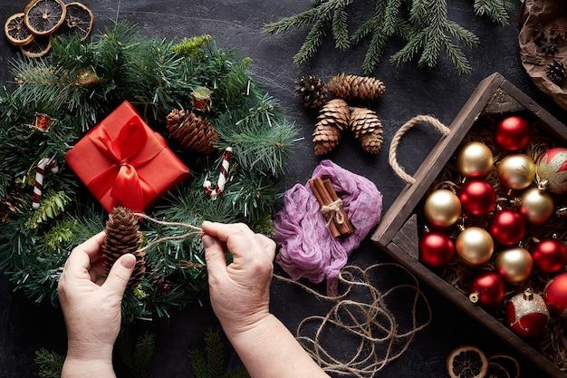 Entrega una corona de navidad y adornos para árboles sobre fondo de hormigón negro