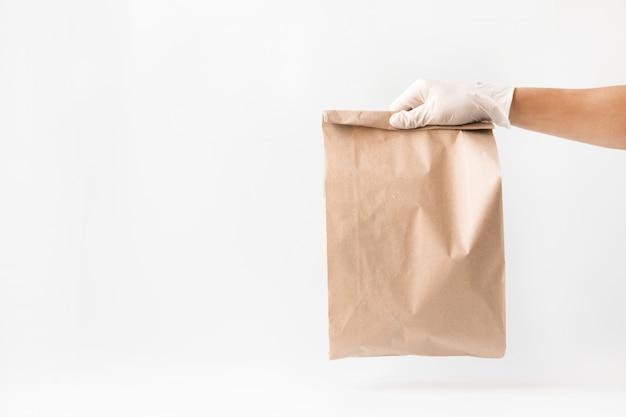 Entrega a domicilio en una bolsa de papel con guantes