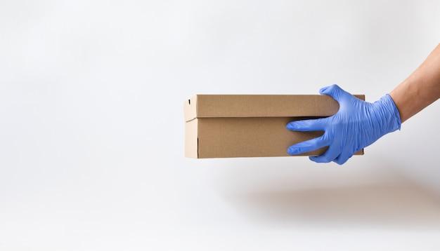 Entrega a domicilio en una caja de papel con guantes