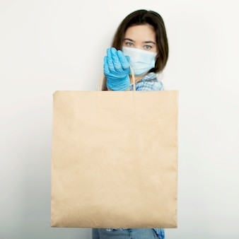 Entrega a domicilio durante coronavirus, brotes virales y pandemias. la muchacha en guantes azules sostiene una bolsa con los productos en un fondo aislado blanco. covid-19