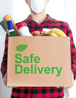 Entrega a domicilio segura. el mensajero entrega una caja de comida.