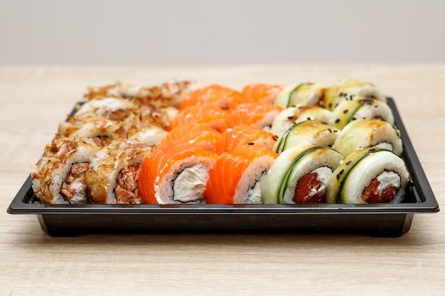 Entrega a domicilio de sushi en caja de plástico.