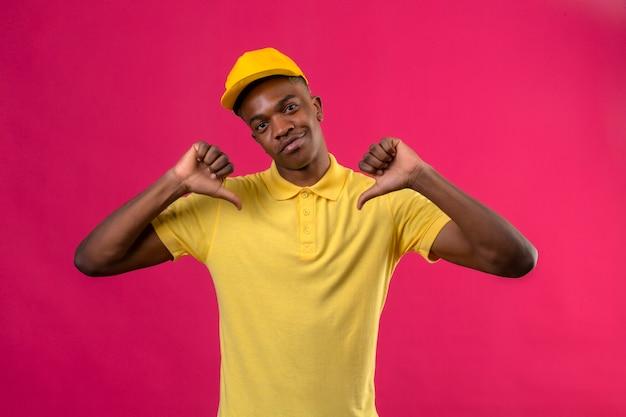 Entrega hombre afroamericano en polo amarillo y gorra mirando confiado apuntando a sí mismo orgulloso auto-satisfecho de pie en rosa