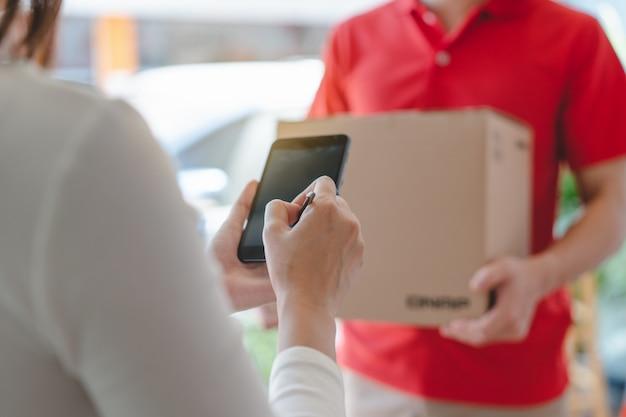 Entrega hombre enviando el paquete al receptor en la puerta.