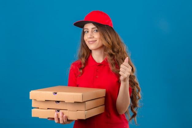 Entrega joven mujer con cabello rizado vistiendo polo rojo y gorra con pila de cajas de pizza sonriendo mostrando el pulgar hacia arriba sobre fondo azul aislado
