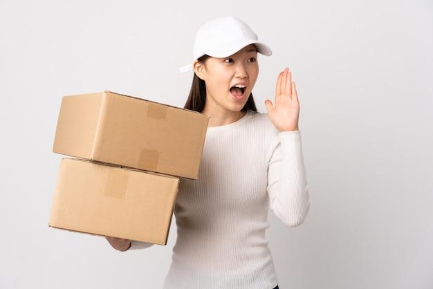 Entrega joven mujer china sobre pared blanca aislada gritando con la boca abierta