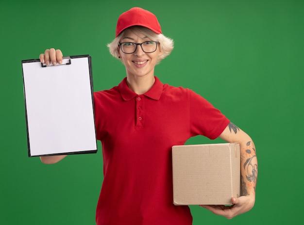 Entrega joven mujer en uniforme rojo y gorra con gafas con caja de cartón que muestra el portapapeles con páginas en blanco sonriendo alegremente de pie sobre la pared verde
