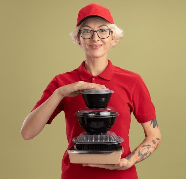 Entrega joven mujer en uniforme rojo y gorra con gafas sosteniendo una pila de paquetes de alimentos sonriendo confiados de pie sobre la pared verde