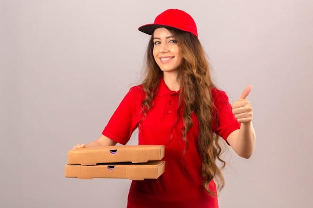 Entrega joven mujer vistiendo polo rojo y gorra de pie con pila de cajas de pizza sonriendo mostrando el pulgar hacia arriba sobre fondo blanco aislado