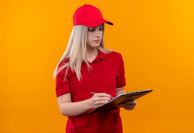 Entrega joven vistiendo camiseta roja y gorra escrita algo en el portapapeles en la pared naranja aislada