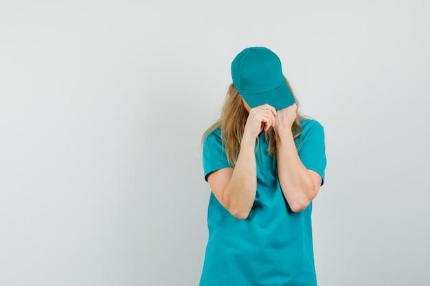 Entrega mujer ajustando gorra en camiseta, gorra y aspecto ordenado.