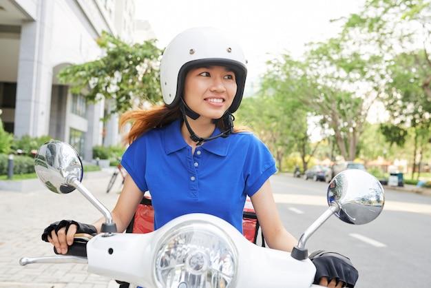 Entrega mujer montando scooter