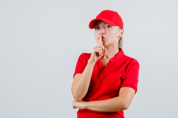 Entrega mujer mostrando gesto de silencio en camiseta roja y gorra y mirando con cuidado