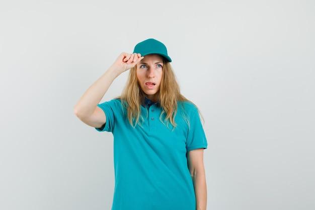 Entrega mujer sosteniendo su gorra en camiseta, gorra y mirando pensativo