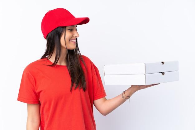 Entrega de pizza mujer sosteniendo una pizza sobre pared blanca con expresión feliz