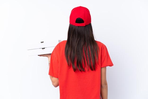 Entrega de pizza mujer sosteniendo una pizza sobre la pared blanca en la posición posterior