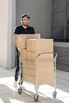 Entrega sonriente caminando sobre el pavimento con la carretilla llena de cajas de cartón