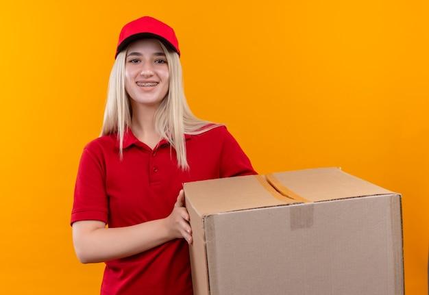 Entrega sonriente joven vestida con camiseta roja y gorra en caja de sujeción de corsé dental sobre fondo naranja aislado