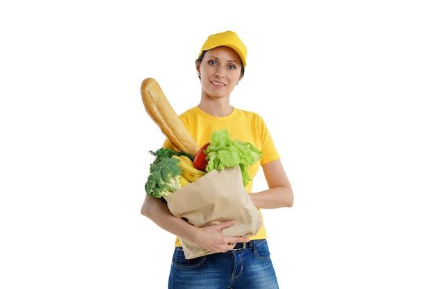 Entrega sonriente mujer en amarillo posando con bolsa de supermercado, fondo blanco.