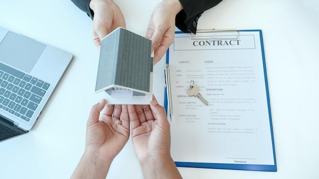 Entregue a un agente de bienes raíces el modelo de la casa y explique el contrato comercial, el alquiler, la compra, la hipoteca, el préstamo o el seguro de la casa a la mujer compradora.