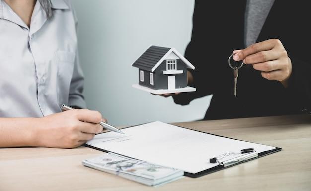 Entregue a un agente de bienes raíces, sostenga las llaves y explique el contrato comercial