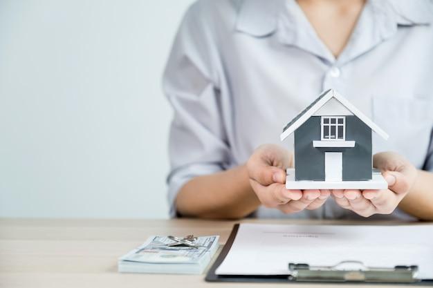 Entregue a un agente de bienes raíces, sostenga el modelo de la casa y explique el contrato comercial,