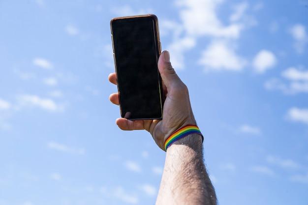 Entregue usando el móvil una pulsera de color lgtb con el cielo de fondo.