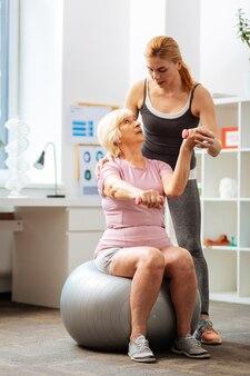 Entrena con un entrenador. senior mujer de pelo gris mirando a su entrenador mientras hace ejercicio