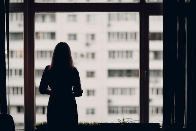 Entrenador adulto joven de mujer de negocios de pie en la silueta de la ventana de la oficina