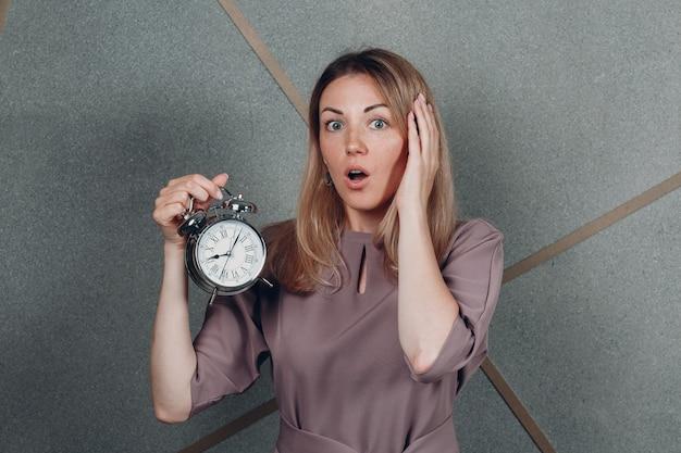 Entrenador adulto joven de la mujer de negocios con el reloj del reloj en el retrato de la oficina. concepto de gestión del tiempo