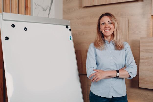 Entrenador adulto joven de la mujer de negocios en el tablero blanco vacío del rotafolio de la plantilla en blanco de la oficina.