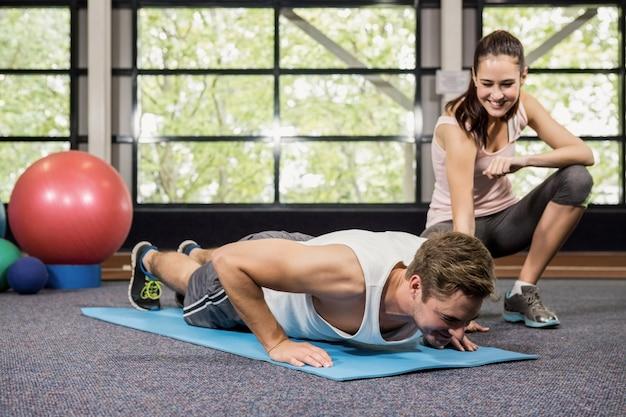 Entrenador ayudando al hombre con flexiones