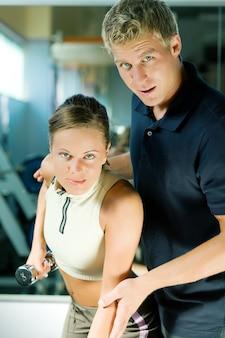 Entrenador ayudando a la chica a hacer ejercicio