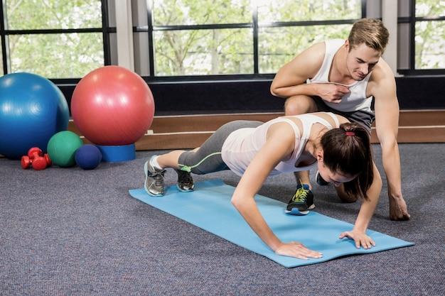 Entrenador ayudando a mujer con flexiones