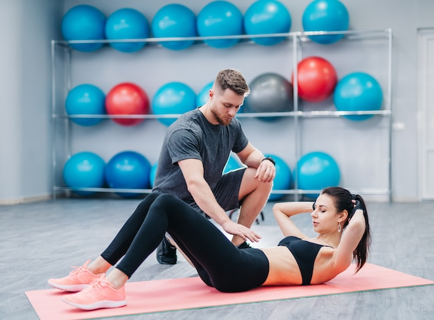 Entrenador ayudando a una mujer joven a hacer ejercicios abdominales en el fondo de pelotas de fitness