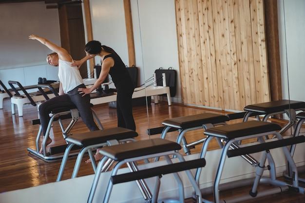 Entrenador ayudando a una mujer mientras practica pilates